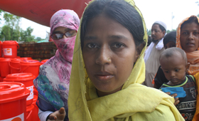 A Rohingya woman receives a UNFPA Dignity Kit with clothing and personal hygiene items